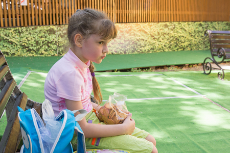 Tired girl in the park sits on a bench with a pack of cookies in her hands