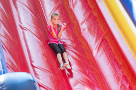 The girl is rolling down from a high soft inflatable trampoline