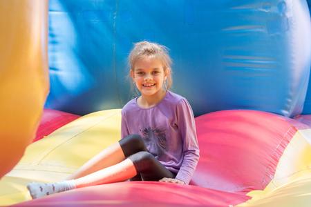 The girl sits on a large soft inflatable trampoline