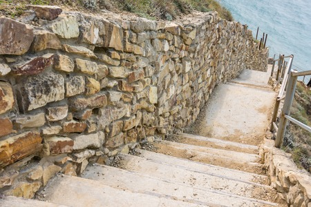 Picturesque steps with a stone fence descending to the sea