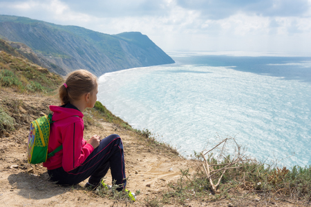 The girl sits on a high bank and looks at the sea