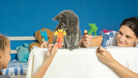 Mom and daughter play a puppet theater with a tired cat