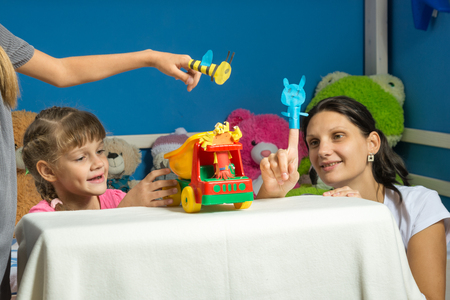 An enthusiastic mother plays with daughters in a self-made finger puppet theater Stock Photo