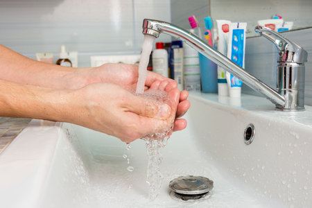 Hands under the tap from the mixer