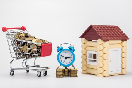 Grocery trolley filled with coins, desk clock and childrens house