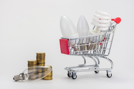 In the grocery cart are LED and energy-saving light bulbs, near the incandescent lamp and stacks of coins Banco de Imagens