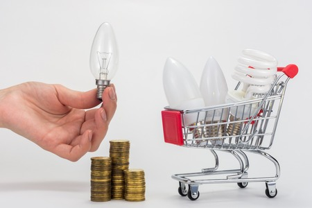 In the grocery cart are LED and energy-saving light bulbs, next to a hand is holding an incandescent lamp, there is a stack of coins