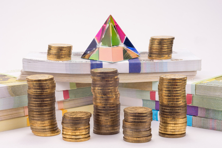 Financial pyramid, wads of money and stacks of coins