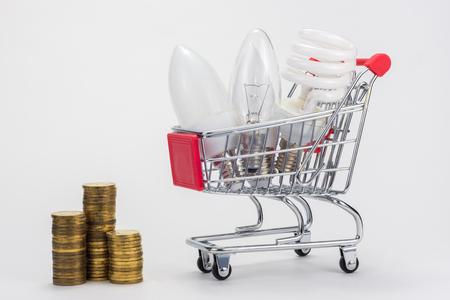 Different LED bulbs, energy-saving, incandescent are in the grocery cart, next to there are stacks of coins