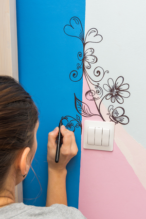 The artist paints a marker patterns on the walls of the childrens room Stock Photo