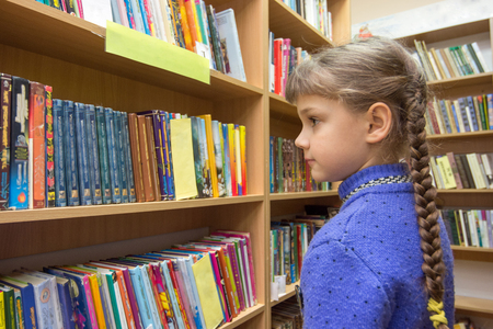 The girl chooses books in the library