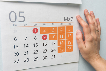 Hand next to the wall calendar