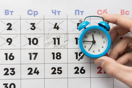 A hand holds a small alarm clock, in the background is a calendar with the day marked and the word vacation