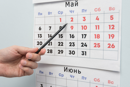 Pencil hand indicates long weekends and holidays on a wall calendar