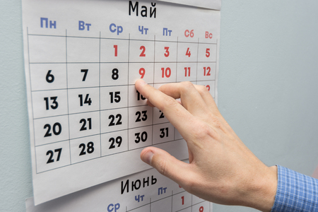 Office workers hand indicates May holidays on a wall calendar sheet Stock Photo