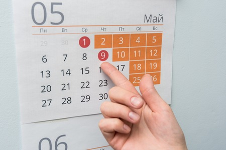 The hand points to the long May holidays holiday in the wall calendar Stock Photo