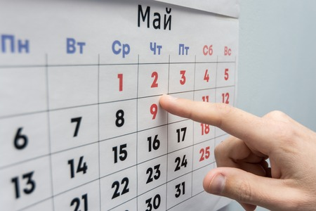 Hand points to the May 2 holiday on a wall calendar sheet