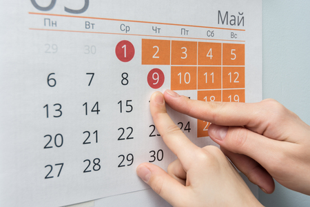 Child and adult hands indicate the date of May 9 wall calendar