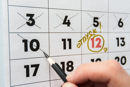 A hand crosses out the penultimate day before the holiday with a pencil in the calendar