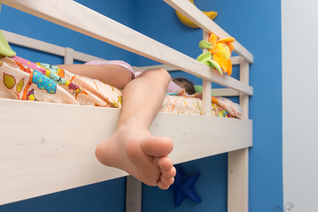 The child sleeps on the second floor of a bunk bed, the leg hangs down