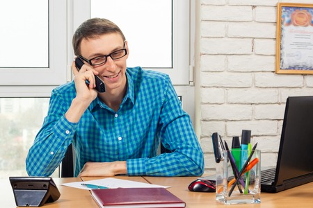 Office specialist with a smile talking on the phone Stock Photo