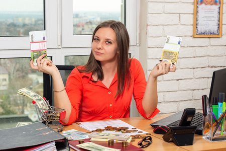 The girl in the office shows bundles of money
