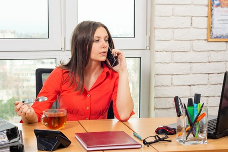An office employee drinks tea at the workplace, talks on the phone and looks at the laptop screen Stock Photo