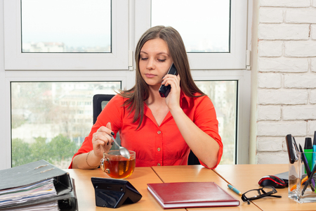 An office employee drinks tea at the workplace and talks on the phone