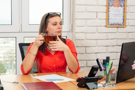 An office employee drinks tea at the workplace and looks at the laptop screen Stock Photo