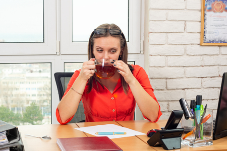 An office employee drinks tea at the workplace at lunchtime