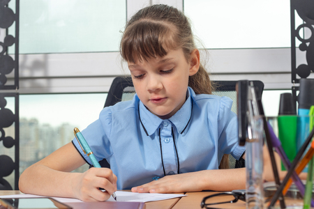 A girl of eight years old is concentrating writing with a fountain pen sitting at a table in an office