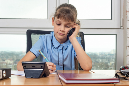 Eight-year-old girl talking on the phone at the table in the office