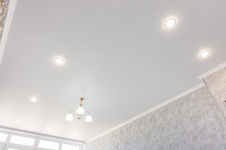 Stretch ceiling in the room with a chandelier and spotlights