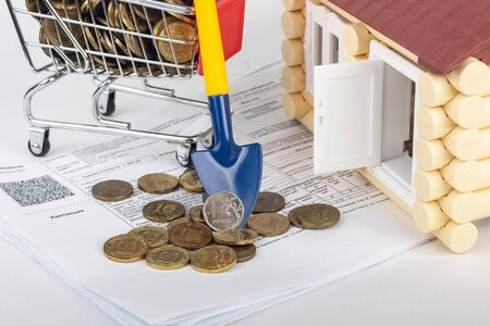 A shovel with a ruble coin rests on a money cart, a number of apartment bills and a toy house Reklamní fotografie