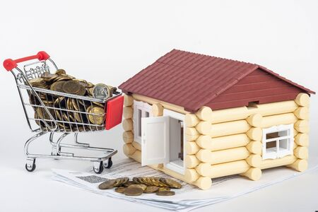 Trolley with money on the bills for the apartment, next to the toy house