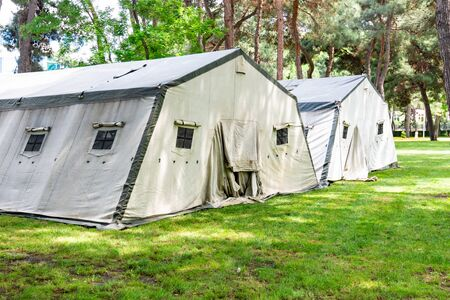 Big tents of the Ministry of Emergency Situations, laid out on the lawn in the forest plantation Stok Fotoğraf