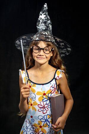 Fille sorcière, avec un livre et une baguette magique, dans un chapeau, sur fond noir Banque d'images