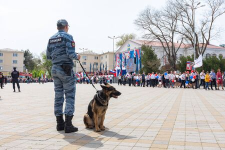 Anapa, Russia - May 1, 2019: A police dog handler with a dog guards a festive May Day demonstration Editorial