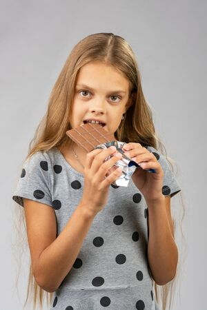 A ten-year-old girl eats a chocolate bar