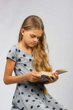Teen girl reads a book
