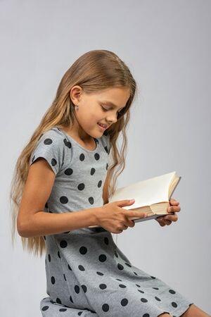 A ten years old girl enjoys reading a book