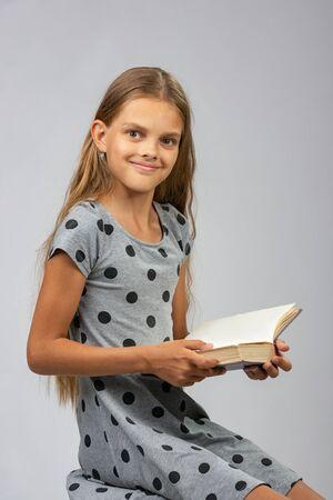 Ein Mädchen von zehn Jahren, das vom Lesen eines Buches abgelenkt wurde und glücklich in den Rahmen schaute Standard-Bild
