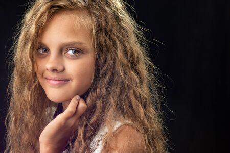 Porträt einer Teenagerin mit langen lockigen Haaren Standard-Bild