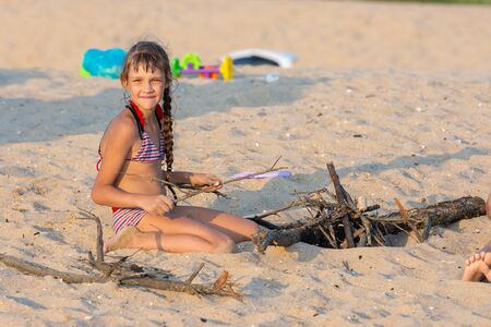 Girl breaks brushwood for a bonfire on a sandy beach and looked into the frame Standard-Bild