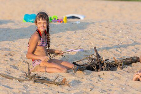 Meisje breekt kreupelhout voor een vreugdevuur op een zandstrand en keek in het frame