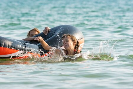 Two girls dive from an inflatable boat into the sea