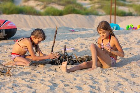 Two girls in the evening on the beach prepare a place for a fire