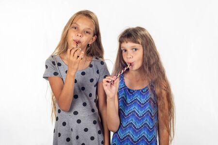 Twee meisjes zuigen lolly's en kijken in het frame Stockfoto