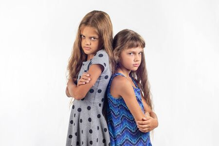 Two offended girls stand with their backs to each other
