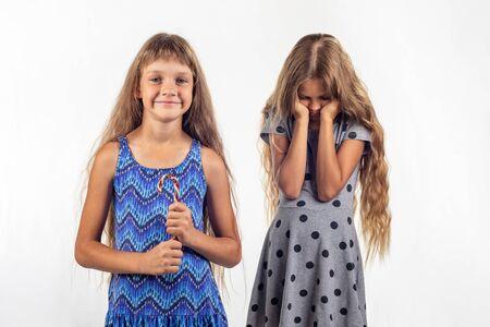 Mädchen hält freudig Süßigkeiten, trauriges anderes Mädchen im Hintergrund